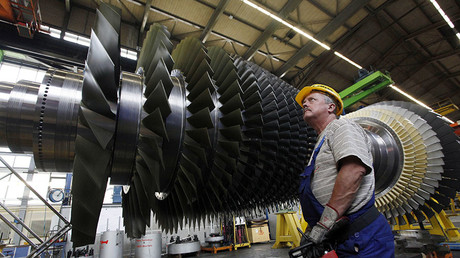 An employee prepares to lift the rotor coil of a Siemens AG Gas Turbine class H is seen at the German industrial giant Siemens historic construction plant in Berlin. © AFP