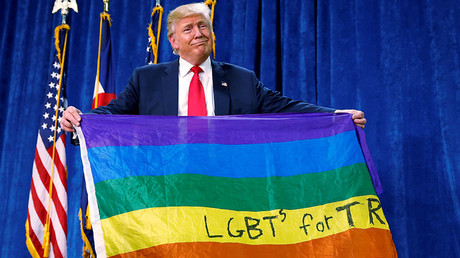 Republican presidential nominee Donald Trump holds up a rainbow flag with
