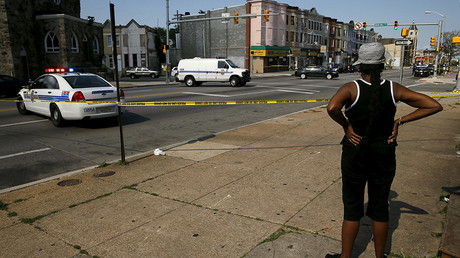 Resident in the neighborhood where Freddie Gray was arrested and where residents rioted over his death in April look on at the scene of a shooting in West Baltimore © Jim Bourg
