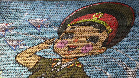 North Korean students use different colored cardboard to form a picture of a child  in uniform, Pyongyang ©Jason Lee