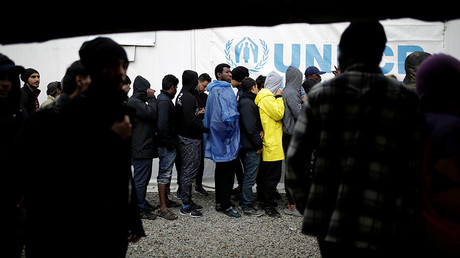 Refugees and migrants line up to receive their lunch provided by the Greek authorities, at a makeshift camp next to the Moria camp on the island of Lesbos, Greece, November 30, 2017. © Alkis Konstantinidis