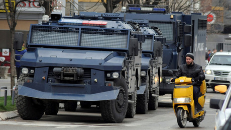 FILE PHOTO: A man rides on a scooter along a street past parked Kosovo police armored vehicles in Kosovo, on March 27, 2018. © Laura Hasani