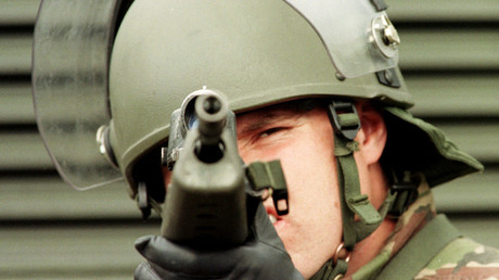 A British soldier peers down the sights of his gun on a morning patrol in East Belfast July 8, 1998. 