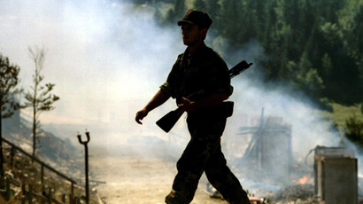 A Bosnian Serb soldier passes a burning house prior to the pullout of Serb forces August 14, 1993 from two heights overlooking Sarajevo, Mount Bjelasnica and Mount Igman (Reuters/Oleg Popov