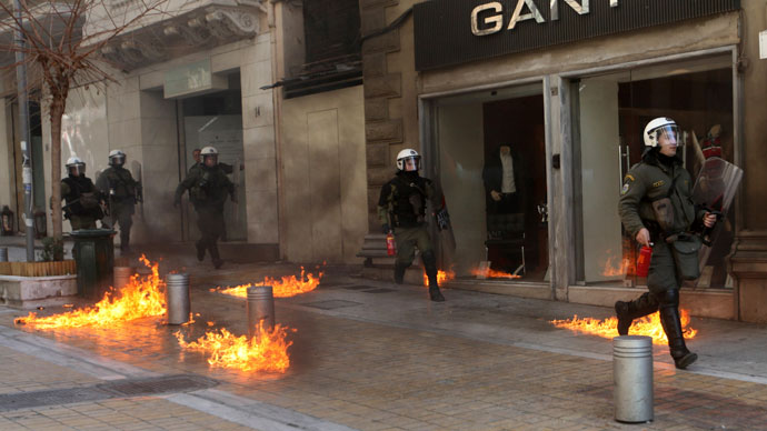 Riot police run by closed shops after protesters threw a petrol bomb following an anti-austerity march during a 24-hour strike in Athens February 20, 2013.(Reuters / Giorgos Moutafis)
