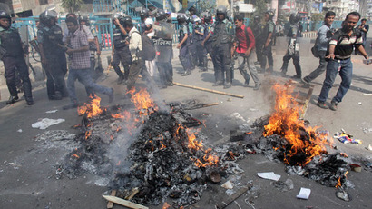 Police walk past piles of paper set alight by activists from 12 Islamist parties in front of the national mosque in Dhaka February 22, 2013.(Reuters / Andrew Biraj)