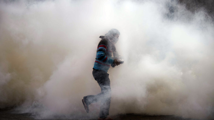 An Egyptian protester attempts to throw back a tear gas canister on November 27, 2012 during clashes with the Egyptian Riot Police in Omar Makram street, off Tahrir Square in Cairo. (AFP Photo/Gianluigi Guercia)