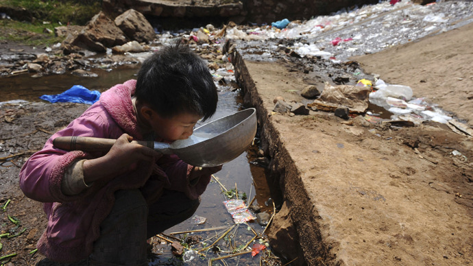 A child drinks water near a stream in Fuyuan county. (Reuters)