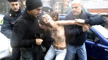 Police stop an activist from the women's rights organisation Femen during a protest outside the polling station where former Prime Minister Silvio Berlusconi cast his vote in Milan, February 24, 2013. (Reuters/Cezaro De Luca)
