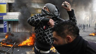 A Palestinian protester throws stones during clashes with Israeli soldiers in the West Bank city of Hebron February 25, 2013 following the funeral of Palestinian prisoner Arafat Jaradat. (Reuters / Mussa Qawasma)