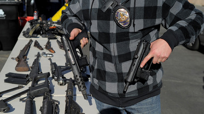 LAPD officer shows assault weapons. (AFP Photo / Joe Klamar)