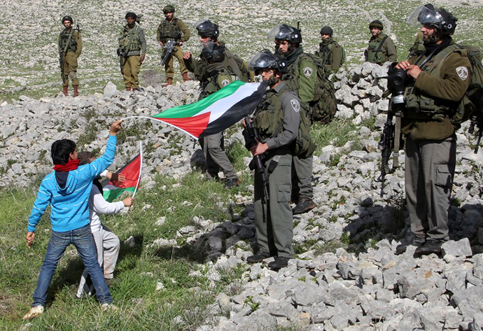 Children wave Palestinian flags in front of Israeli security forces as Palestinians set up a new camp to protest against Jewish settlements near the West Bank village of Burin on February 2, 2013. (AFP Photo / Jaafar Ashtiyeh)