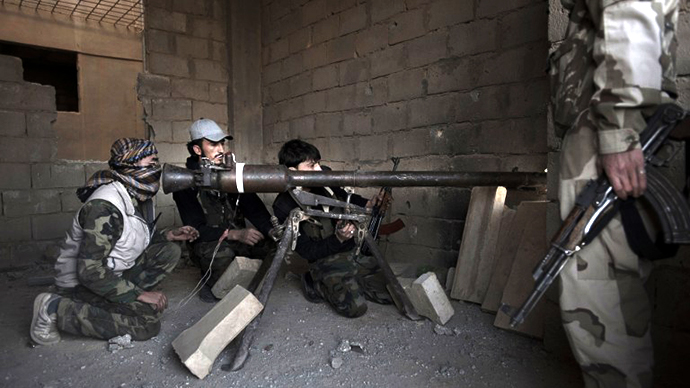 Rebels fighters prepare to fire a portable canon against an adjacent Syrian government-held building during fighting on February 27, 2013. (AFP Photo / Zac Ballie)