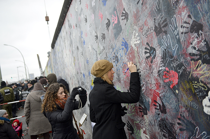 A woman writes on a part of the East Side Gallery. (AFP Photo / Odd Andersen)