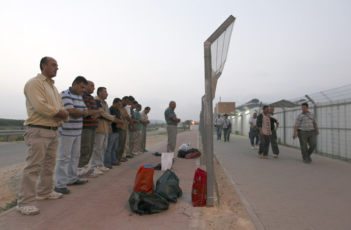 Palestinian labourers pray after crossing through Israel's Eyal checkpoint near the West Bank town of Qalqilya (Reuters/Baz Ratner)