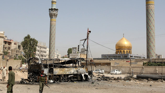 A general view shows a bombed bus outside a Shiite holy shrine in the Sayyida Zeinab suburb of Damascus, after a suicide car bomb exploded there early on June 14, 2012, wounding at least 14 people and damaging one of Shiite Islam's holiest shrines, Syrian state media and witnesses reported. (AFP Photo/Louai Beshara)