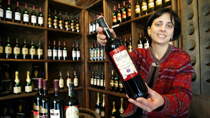 A sales woman displays a bottle of Georgian wine. (AFP Photo / Vano Shlamov)