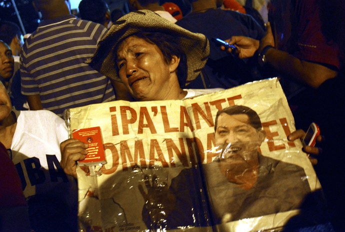A supporter of Venezuelan President Hugo Chavez shows a sign with his portrait outside the Military Hospital in Caracas next to Army members on March 5, 2013, after knowing of his death (AFP Photo / Leo Ramirez)