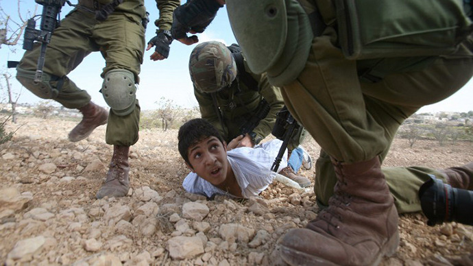 A Palestinian youth is arrested by Israeli soldiers for throwing stones during a protest. (AFP Photo / Hazem Bader)