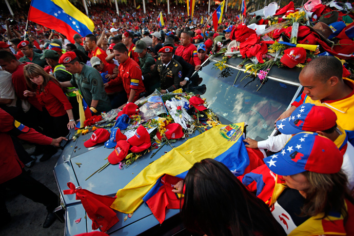 Caps and posters of late Venezuelan leader Hugo Chavez lie on the hood of the hearse that carried his coffin to the Military Academy, where his wake will be held, in Caracas March 6, 2013 (Reuters / Jorge Silva)