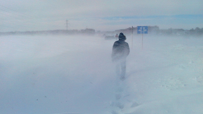 A driver walks through the snow in Novosibirsk Oblast after his car got stuck in the road along with about 100 others (RIA Novosti / Artur Gutman)