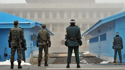 South Korean soldiers stand guard in fog as a North Korean soldier (C far) is seen at the truce village of Panmunjom in the demilitarized zone dividing North and South Korea (AFP Photo / Jung Yeon-Je)
