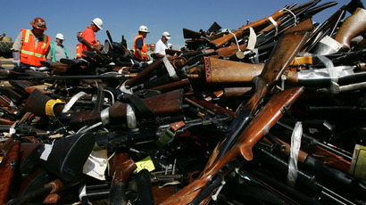 Steel workers look over a pile confiscated illegal weapons in  Rancho Cucamonga, California (AFP Photo / David McNew)