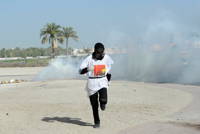 A protester runs to take cover from tear gas fired by riot police during early hours of clashes in the village of Sanabis, west of Manama March 14, 2013 (Reuters / Hamad I Mohammed)