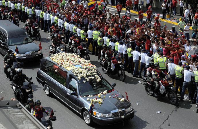 "The hearse carrying the remains of late Venezuelan President Hugo Chavez heads to his resting place at the former ""4 de Febrero"" barracks -- a barracks-turned-museum that the former paratrooper had used as his headquarters during a failed 1992 coup attempt -- in Caracas, on March 15, 2013.(AFP Photo / Luis Camacho)"