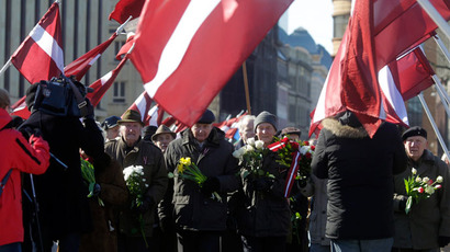 Men holding flowers take part in the annual procession commemorating the Latvian Waffen-SS (Schutzstaffel) unit, also known as the Legionnaires, in Riga March 16, 2013.(Reuters / Ints Kalnins)