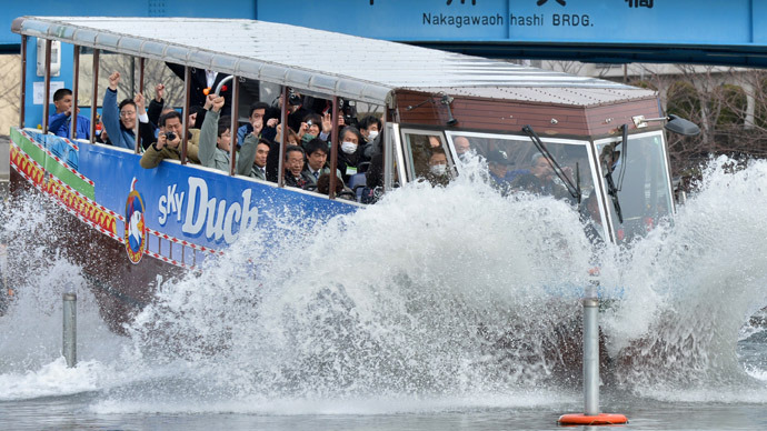 "An amphibious bus ""SKY Duck"" goes into the water during its trial run in Tokyo on February 22, 2013. (AFP Photo/Kazuhiro Nogi)"