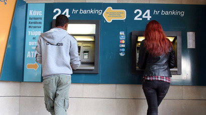A man and a woman withdraw money from a cash-point machine in the Cypriot capital Nicosia on March 16, 2013.  (AFP Photo/Hasan Mroue)