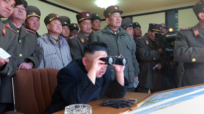 This undated photo released by North Korea's official Korean Central News Agency (KCNA) via the Korean News Service (KNS) on March 14, 2013 shows North Korean leader Kim Jong-Un (C) using binoculars to inspects the Jangjae Islet defence detachment and the Mu Islet defence detachment to guide a live shell firing drill at an unconfirmed location. (AFP Photo/KCNA/KNS)