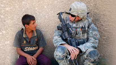 1st Lieutenant Jeffrey Wismann speaks with an Iraqi boy during a combined foot patrol in Salman Pak, near Baghdad, September 12, 2009. (Reuters/U.S. Army/Sgt. 1st Class Alex Licea/Handout)