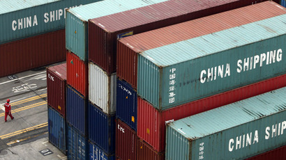A worker walks in a shipping container area at the Port of Shanghai (Reuters/Aly Song)