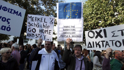Cypriots hold signs, including one bearing the EU flag with the stars in the shape of a swastika, during a protest against an EU bailout deal outside the parliament in Nicosia on March 18, 2013. (AFP Photo / Patrick Baz)