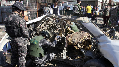 Iraqi policemen examine the remains of a car bomb in Baghdad's Sadr City March 19, 2013. (Reuters/Qahtan al-Sudani)