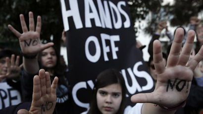 "Protesters raise their open palms showing the word ""No"" during an anti-bailout rally outside the parliament in Nicosia March 18, 2013. (Reuters/Yorgos Karahalis)"