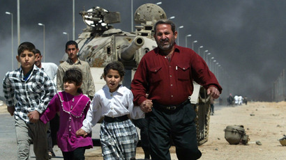 A family flees past a destroyed Iraqi T-55 tank after a mortar attack on British Army positions in the southern city of Basra March 28, 2003. (Reuters/Chris Helgren)