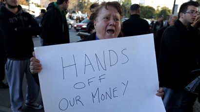 A Cypriot woman shouts slogans as she holds a placard during a protest against an EU bailout deal outside the parliament in Nicosia (AFP Photo / Patrick Baz)