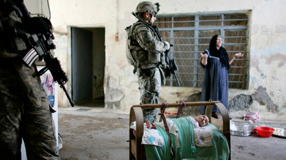 An Iraqi baby lies in a cradle while a woman argues with U.S. soldiers of 1/8 Bravo Company searching for weapons, explosives and information about militants in the area during a foot patrol in a neighbourhood of Mosul June 26, 2008 (Reuters / Eduardo Munoz)