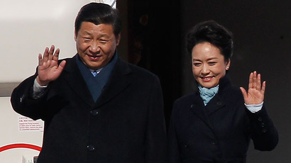 Chinese President Xi Jinping (L) and First Lady Peng Liyuan wave as they disembark from a plane upon their arrival at Moscow's Vnukovo airport March 22, 2013.(Reuters / Maxim Shemetov)