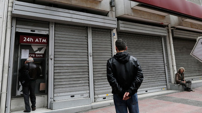 People wait to make transactions at an ATM machine as a man (R) begs outside a closed Cyprus Popular Bank (CPB) branch in Athens March 21, 2013.(Reuters / John Kolesidis)