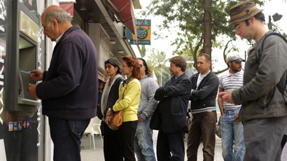 People queue outside a Laiki (Popular) Bank branch in the Cypriot capital Nicosia to withdraw money from an ATM cash machine.(AFP Photo /Patrick Baz)