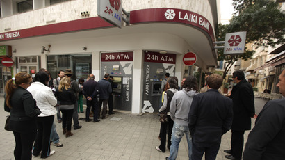 Cypriots and foreigners wait in line to withdraw money from an ATM of a Laiki (Popular) Bank branch in the old city of the capital, Nicosia (AFP Photo / Patrick Baz)