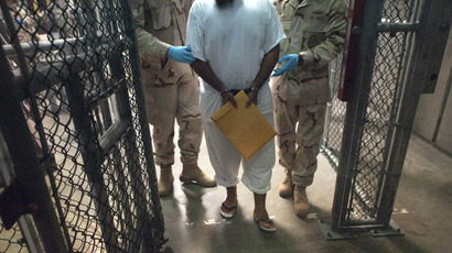 US military guards move a detainee inside Camp VI at Guantanamo Bay, Cuba, on March 30, 2010.  (AFP Photo/Paul J. Richards)