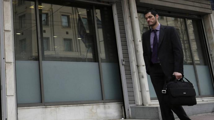 A man walks outside a closed Bank of Cyprus branch (Reuters/John Kolesidis)