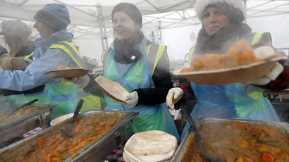 Volunteers prepare plates of food to give away free at lunchtime in Trafalgar Square in London (Reuters/Andrew Winning)