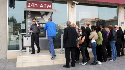 Cypriots and foreigners wait in line to withdraw money from an ATM of a Laiki (Popular) Bank branch in the centre of the capital, Nicosia (AFP Photo / Hasan Mroue)