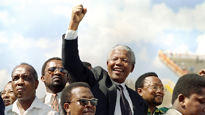A file photo taken on March 15, 1994 shows the President of the African National Congress (ANC) Nelson Mandela raising a clenched fist to supporters upon his arrival for an election rally ahead of the April 27 general elections in Mmabatho. (AFP Photo / Walter Dhladhla)